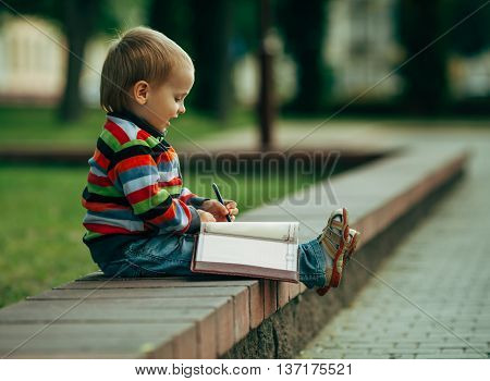 photo of little funny boy writing with pen