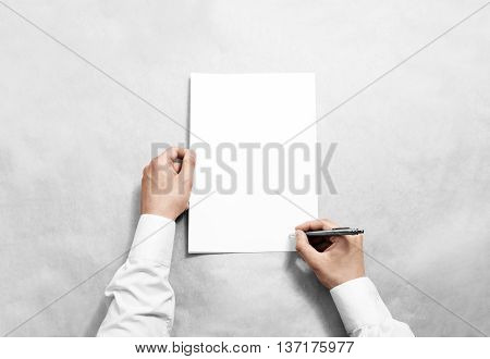 Hand hold blank contract mockup and signing it. Arm in shirt holding clear document template mock up. Agreement surface design. Simple pure legal paper print display. Reading contract statement.