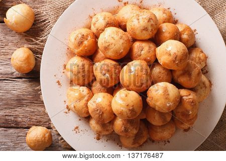 poster of Greek loukoumades donuts with honey and cinnamon close-up on a plate. horizontal view from above