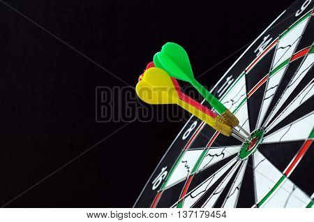Three darts hits on dartboard target with black background.