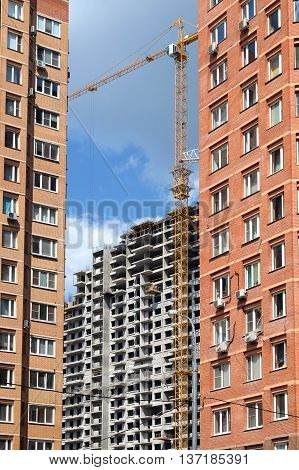 Construction of city district. Constructed brick houses in the foreground and construction building from concrete on the far. Photo in sunny day vertical view