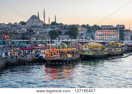 ISTANBUL TURKEY - JUNE 20 2015: Night view from Galata Bridge towards the Suleymaniye Mosque and fishing boats in Eminonu district Istanbul Turkey
