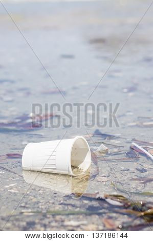 White abandoned plastic cup on the beach. Pollution.