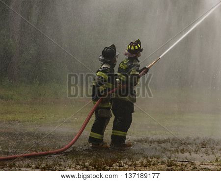 Buena Vista, New Jersey  USA  JULY 2, 2016 Two Firefighters spraying a hose.