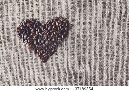 Burlap texture with coffee beans heart shape background, love symbol. Stained sack cloth canvas with copy space. Seeds at hessian textile, soft color toning