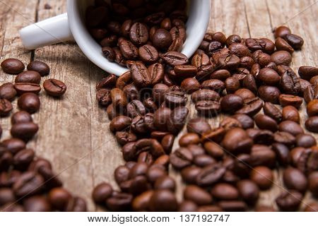 Cup with roasted coffee beans. Coffee grains of dark color. Fresh aroma of arabica. Cup on old brown shelf.