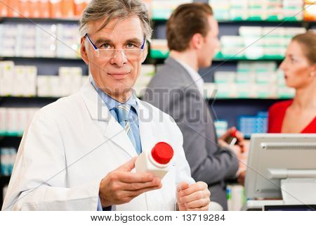 Pharmacist with customers in pharmacy, he is holding a bottle with pharmaceuticals in his hand