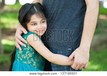 Closeup portrait young child hugging her father tenderly isolated outdoors outside green grass background. Daddy's little girl