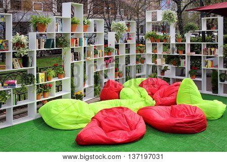 MOSCOW - MAY 02, 2015: Shelves with books around colored soft puffs at Sokolniki area on Moscow Spring Festival