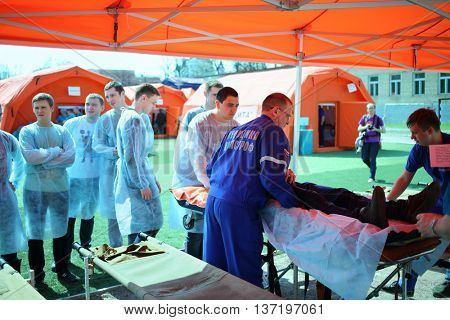 MOSCOW - APR 28, 2015: A group of students watching the transportation of the injured person during a training exercise at a field hospital on the Burevestnik stadium
