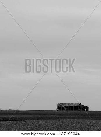Single barn on stark horizon, cloudless sky