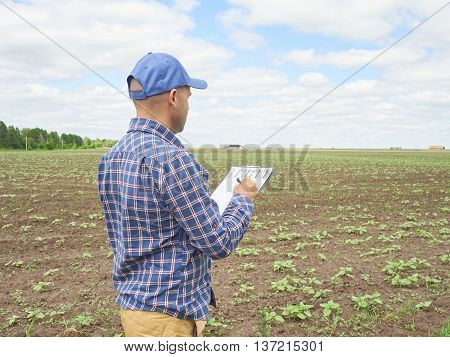 Farmer In Plaid Shirt Controlled His Field And Writing Notes