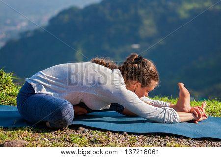 Yoga outdoors - woman doing Ashtanga Vinyasa yogaJanu Sirsasana A head to knee stretching asana position outdoors