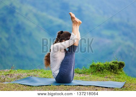 Yoga - sporty fit woman practices Ashtanga Vinyasa yoga asana Urdhva mukha paschimottanasana - upward facing intense west stretch oudoors