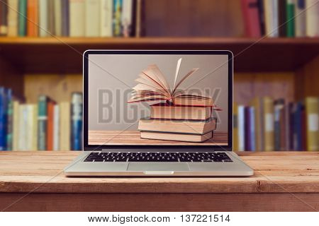 E-book library concept with laptop computer and stack of books on wooden table