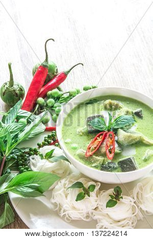 Green curry creamy coconut milk with chicken the Popular Thai food called Gaeng Keow Wan Gai on wooden table