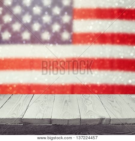 Empty wooden white table over USA flag bokeh background. USA national holidays background. 4th of July celebration. Ready for product display montage.