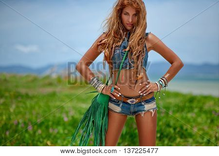 Beautiful hippie girl in denim clothes on the beach