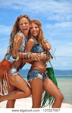 Two beautiful hippie girls in denim clothes outdoors