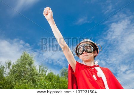 Low angle view of cute teenage boy wearing metal colander as a helmet goggles and red costume pretending to be a power super hero