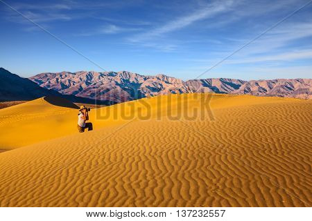 Woman in striped shirt and straw hat  photographing sand waves. Bright morning in picturesque part of Death Valley. Mesquite Flat Sand Dunes