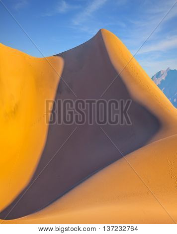 Bizarre twists of orange sand dune. Bright sunny morning in a Death Valley, USA. Mesquite Flat Sand Dunes