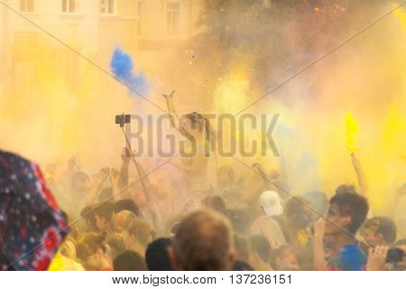 Holi festival color explosion. A large number of people celebrating the Indian Holi festival, throwing colored paint paint. Multi-colored dust from the paint over the crowd of happy people
