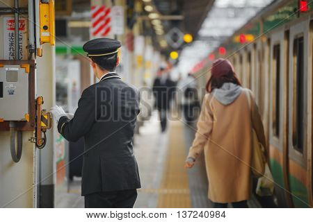 Tokyo, Japan - November 29 2015: An Unidentified Japanese Train Conductor Is On His Duty On A Platfo