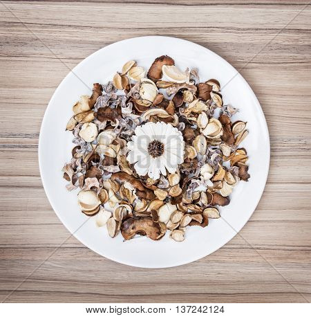 Decoration of dried flowers on the white plate. Natural beauty. Spa theme. Potpourri scene.