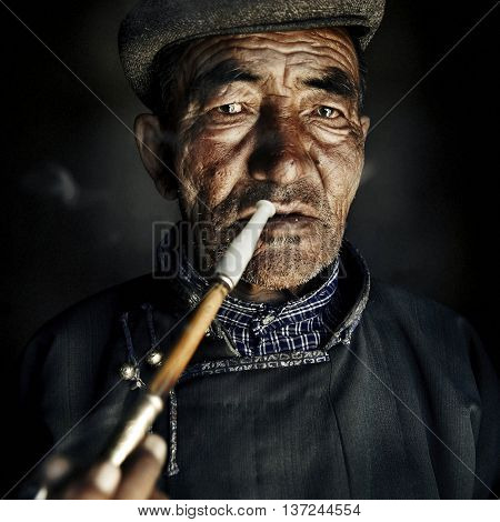 Mongolian Man in Traditional Dress Smoking a Pipe Concept