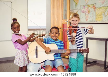 Portrait of smiling kids playing guitar, violin, flute in classroom at school