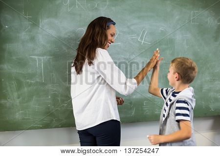 Happy teacher and school boy giving high five in classroom at school