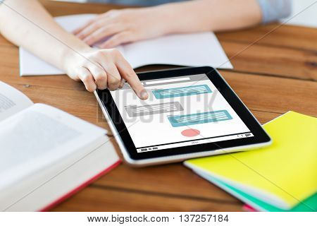 internet communication, education, technology and internet concept - close up of student woman with messenger on tablet pc computer screen and notebook at home