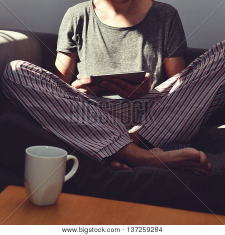 closeup of a mug with coffee or tea on a coffee table and a young caucasian man in pajamas using a tablet computer seating in a couch