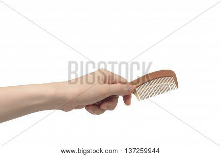 hand holding brown comb on white background.