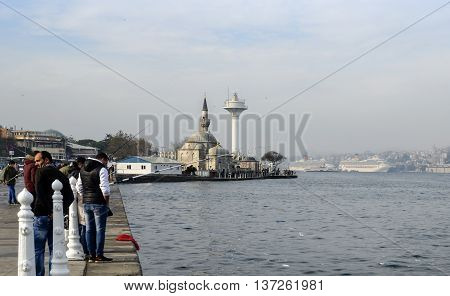 Istanbul Turkey - November 9 2014: Istanbul at the Bosphorus bonito bluefish mackerel sardines sea bass and other bottom fish hunt. Migration time increases in fishing catch fish. Üsküdar Shamsi Pasha Mosque is seen in the background.