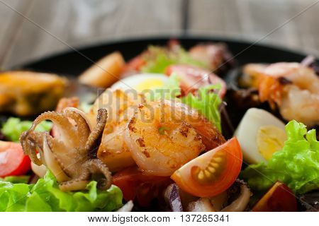 Grilled shrimp, octopus, quail egg in salad closeup. Extreme close-up of grilled seafood salad on wood with quail eggs and tomatoes. Healthy eating, creative food concept