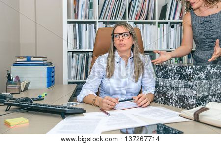 Portrait of exhausted blonde secretary blowing with lot of work waiting in her desktop