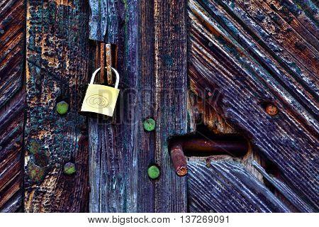 Rotting wooden barn door locked with yellow lock alongside a rusty handle.