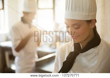 Happy head chef cooking at stove in a commercial kitchen