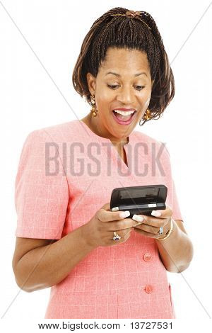 Beautiful african-american businesswoman laughing as she reads a text message on her smart phone.  Isolated on white.