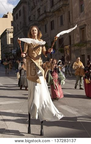 Enna, Italy - May 2016: Stilt walker woman takes part in the medieval costume parade along the street. Tenth Edition of Historical Parade, 15 may 2016, Enna, Sicily