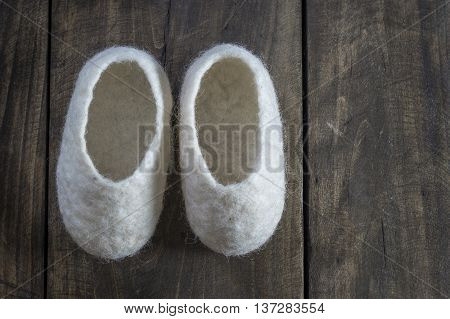 Comfortable wool home Baby Booties on wooden background
