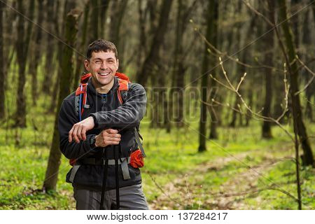 Hiker wearing hiking backpack and jacket on hike in forest. Man using hiking sticks poles outdoors in woods. Male hiker standing looking away.