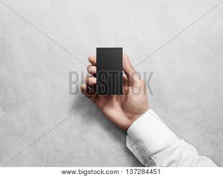 Hand holding blank vertical black business card, design mockup. Clear calling card mock up template hold arm. Visiting pasteboard paper surface display front. Grey check card holder presentation