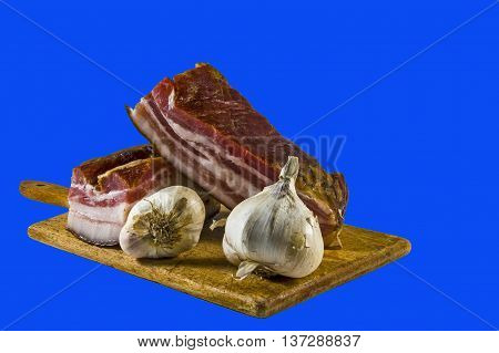 Domestic bacon and garlic on wooden kitchen board.