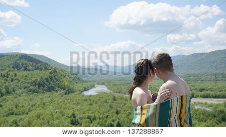 Young seductive naked couple covered by blanket softly embrasing on the green mountains background.