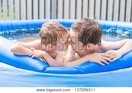 happy children having fun in the inflatable pool. funny kids rub noses and playing in the inflatable swimming pool in the garden. nose to nose, side view
