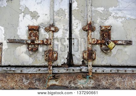 Close-up of old rusty vertical latch on rusty doors