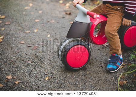Close-up of children bicycle with a child sitting on it. Modern kid's plastic bicycle on the road. First transport for a boy. Outdoors activities for active children.